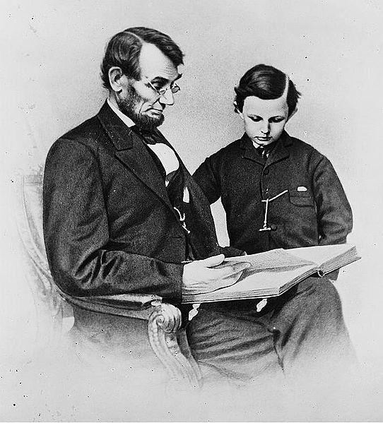 Abraham Lincoln and his son Tad looking at an album of photographs