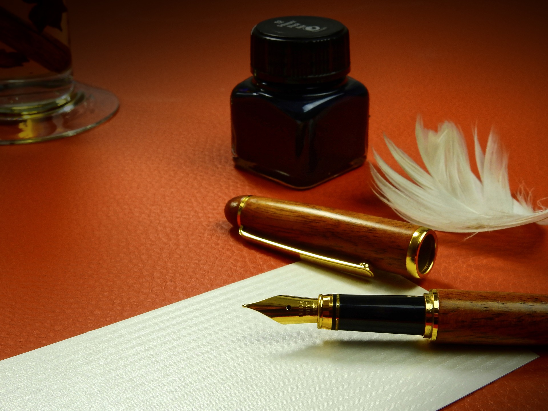 classic ink pen, liquid ink in jar, writing paper, feather, Idris Elba quote,